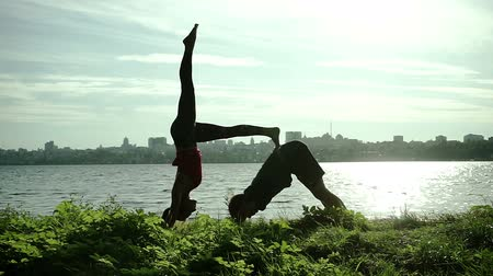 margem do rio : River bank. Young man and woman warming up before practice of acrobatic yoga. HD
