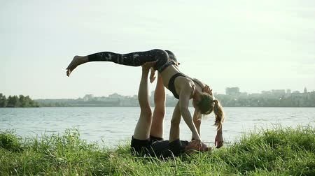 margem do rio : Acrobatic yoga on the bank of the river. Stretching and massage after training. Wide angle. HD Stock Footage