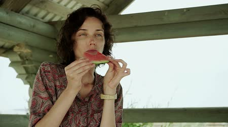 olhos verdes : Young attractive dark-haired woman appetizing eating juicy watermelon. HD