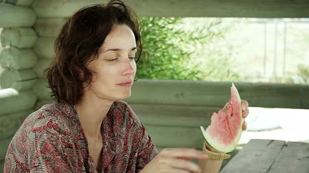 braces : Young attractive dark-haired woman appetizing eating juicy watermelon. HD