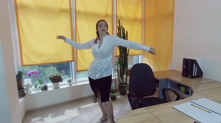 üzleti öltöny : Working day. Pretty young brown-haired woman dancing at the desk in a office. 4K