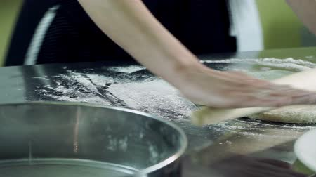 alaplap : Cooking a pizza. The female hands rolling out a dough with a rolling wooden pin. HD