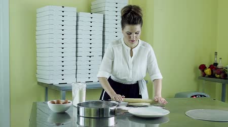 alaplap : Cooking a pizza. Pretty young woman rolling out a dough with a rolling pin. HD Stock mozgókép