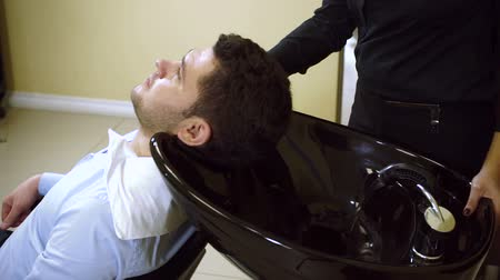 lavatório : Preparing for the haircut. Female barber washing the head of a young man. HD