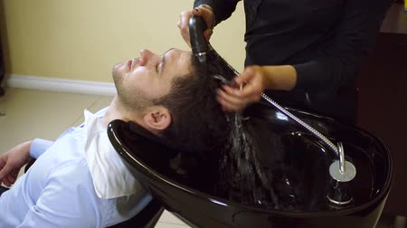 hajápoló : Preparing for the haircut. Female barber washing the head of a young man. HD