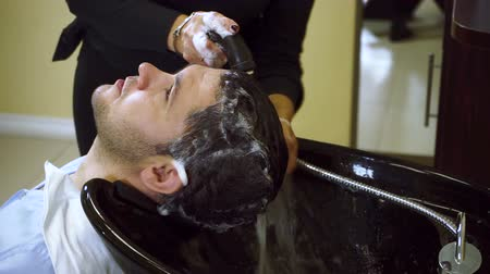 салон : Preparing for the haircut. Female barber washing the head of a young man. HD