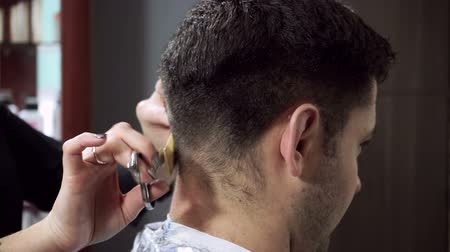 cutting up : Hair-cutting at barbers. Female blonde hairdresser cutting hair of dark-haired man at beauty parlour. HD