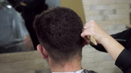 kadeřník : Hair-cutting at barbers. Female blonde hairdresser cutting hair of dark-haired man at beauty parlour. HD