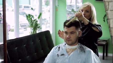 corte de cabelo : Hair-cutting at barbers. Female blonde hairdresser cutting hair of dark-haired man at beauty parlour. HD