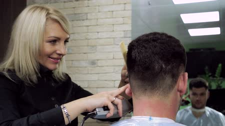 kadeřník : Haircut at barbers. Female hairdresser shaping mens hair into a style by cutting. HD