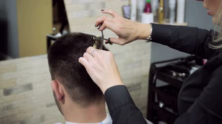 cutting up : Haircut at hairdressers. Beautiful blonde woman cutting mens dark hair. HD