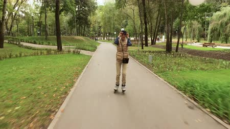 roller blading : Roller skates. Female roller-skater practicing inline skating in the autumn park. 4K Stock Footage