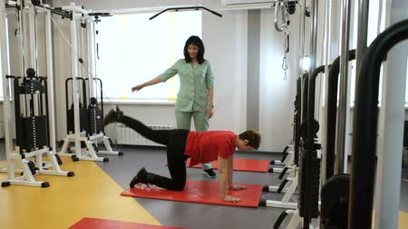 scoliosis : The sports adult woman lifting weights by her legs on fitness equipment with the instructor at gym. HD