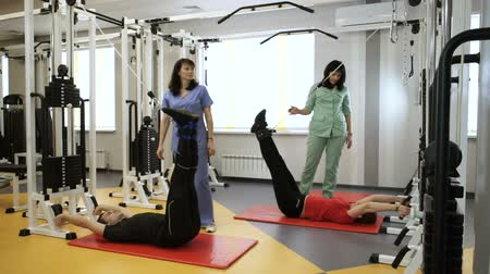 scoliosis : The woman and man lifting weights by their legs on fitness equipment with the instructor at gym. HD