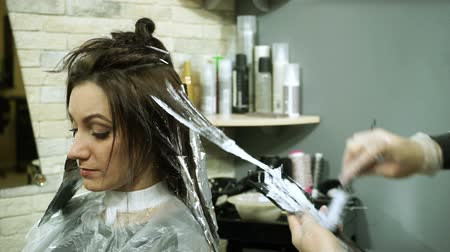 fryzjerstwo : Hair coloring. Dark-haired young woman is colouring her hair in a barber shop. HD