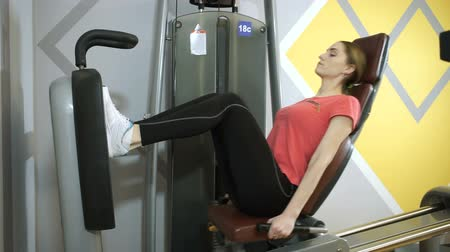 scoliosis : The young slim pretty woman doing fitness training on exercise equipment at sports gym. HD