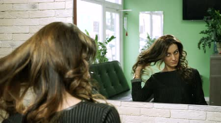 barbering : The young woman looking at her reflection in the mirror on hair shaped into a style by setting at hairdressers. HD