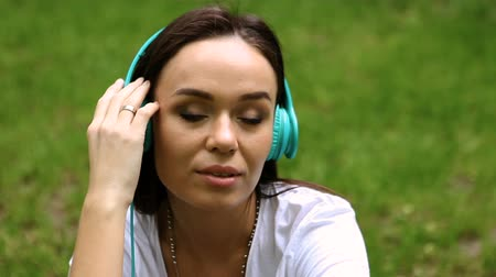 earpiece : Cute dark-haired young woman listening to the music on headphones in the park on a sunny day. HD Stock Footage