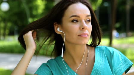 earpiece : Pretty dark-haired young woman listening to the music on headphones in a park on a sunny day. HD