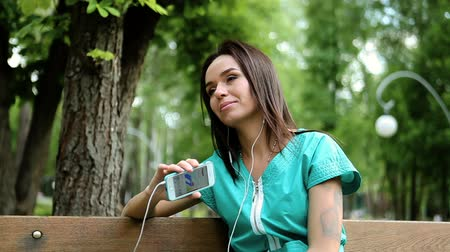 earpiece : Pretty dark-haired young woman listening to the music on headphones in a park HD