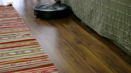 vakum : The robot cleaner cleaning the laminate flooring in the room. 4K Stok Video