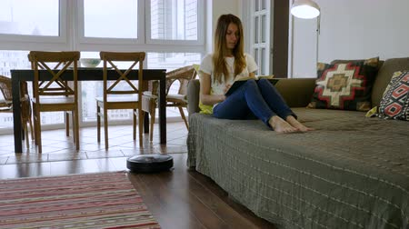 robots : The young pretty woman reading a book while automatic vacuum cleaner cleaning the floor in the room. 4K