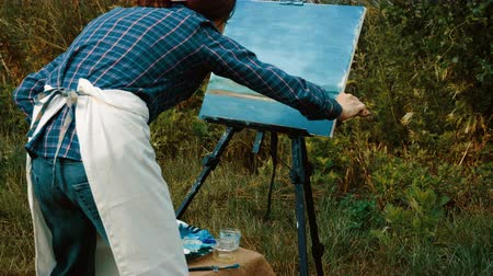 pallette : Landscape painter. A young brilliant artist painting a natural scenery with oil paints. 4K