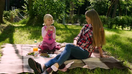 сестра : Two sisters on a picnic outdoors. The little blond girl drinking juice and holding the thumb upwards. 4K Стоковые видеозаписи
