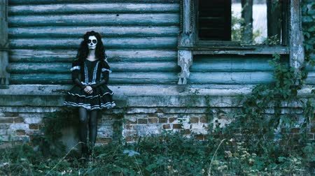 yanmış : The Mexican Day of the Dead. The young woman with frightening make-up for Halloween dressed in black clothes standing in front of abandoned burned wooden house. 4K