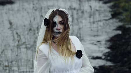 ведьма : The young woman with frightening make-up of dead bride for Halloween dressed in a white wedding gown going through the field of dried grass. Slow motion. HD