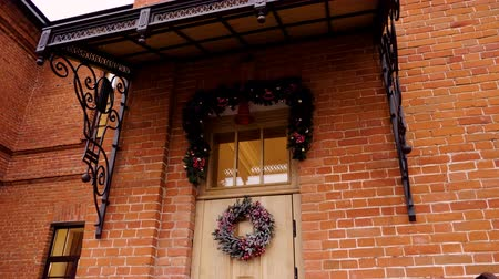 dom : Christmas wreath hanging on a beige wooden front door. 4K Wideo