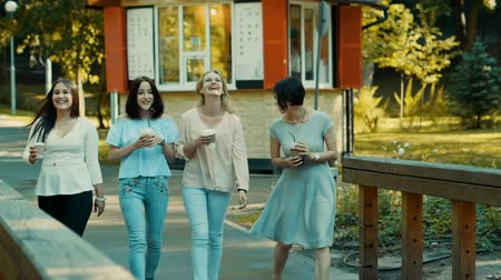 quatro : Four young beautiful women walking in a park, talking and drinking coffee. Slow motion. HD