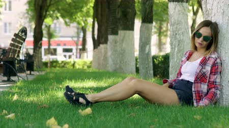 шорты : Beautiful young woman in sunglasses sitting under tree on the green grass at city park. 4K