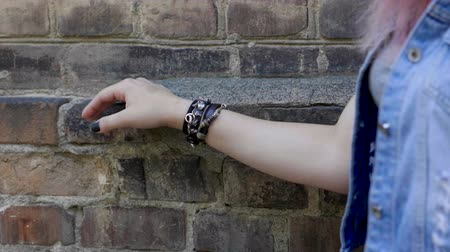 wristband : Womens hand with a black wristband moving along the brick wall. Slow motion. HD