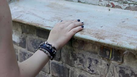 гот : Womens hand with a black wristband moving along the brick wall. Slow motion. HD