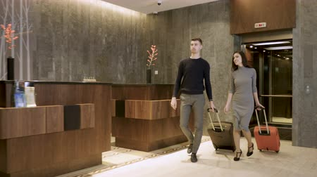 медовый месяц : Attractive happy couple arriving at hotel and going to the reception lobby from elevator to check in. 4K Стоковые видеозаписи