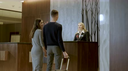 vendég : Happy young attractive man and woman checking in at the reception area in luxury hotel. 4K