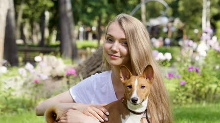 hugs : Pets. Young adorable blonde woman stroking her basenji dog Slow motion. HD Stock Footage