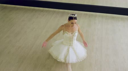 tiara : Dance of ballerina. Graceful female ballet dancer doing a workout in pointe shoes in the classroom. 4K