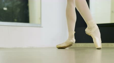 stockings : Close-up shot of feet of female ballet dancer dancing on tiptoe in pointe shoes in studio. 4K