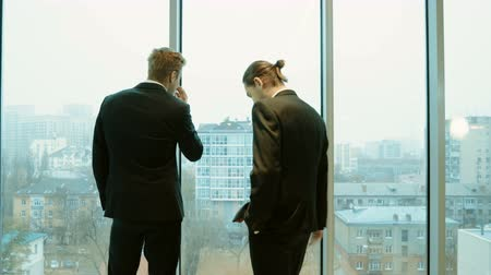 munkatárs : Rear view of two men in business suits standing in front of panoramic window with city view and talking. 4K