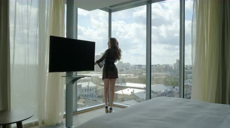 koronka : Beautiful blonde young woman in black lingerie standing at the panoramic window in a luxury room. 4K Wideo