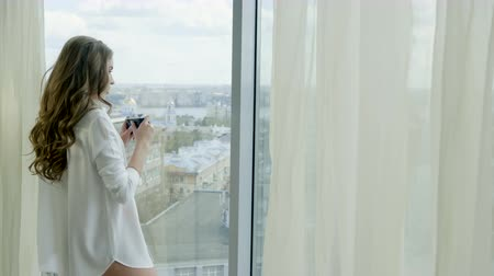 külot : Medium shot of beautiful blonde woman in red lingerie and white shirt taking photos of city view from the panoramic window of the hotel room. 4K