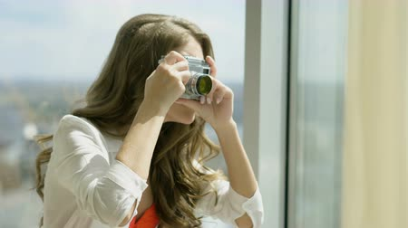 sutiã : Portrait of beautiful blonde woman taking photos of city view from the panoramic window of the hotel room. 4K