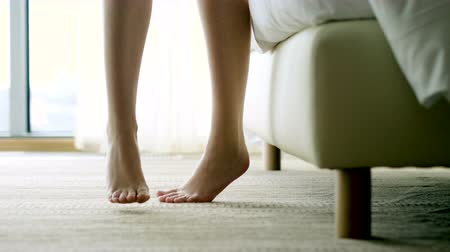 barefooted : Close-up shot of slender bare female legs in the interior of the bedroom. 4K