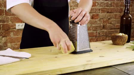 пармезан : The cook rubbing parmesan cheese on the metal grater for pesto sauce. 4K Стоковые видеозаписи