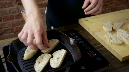 being cut up : Close-up shot of four slices of baguette are being fried in a grill pan for italian bruschetta. 4K