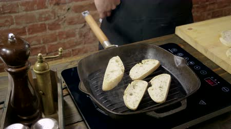 being prepared : Close-up shot of four slices of baguette are being fried in a grill pan for italian bruschetta. 4K