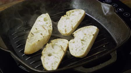 стартер : Close-up shot of four slices of baguette are being fried in a grill pan for italian bruschetta. 4K