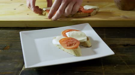 bruschetta : Chef cooking italian food. Bruschetta with tomatoes, mozzarella cheese, pesto sauce, green onion. 4K